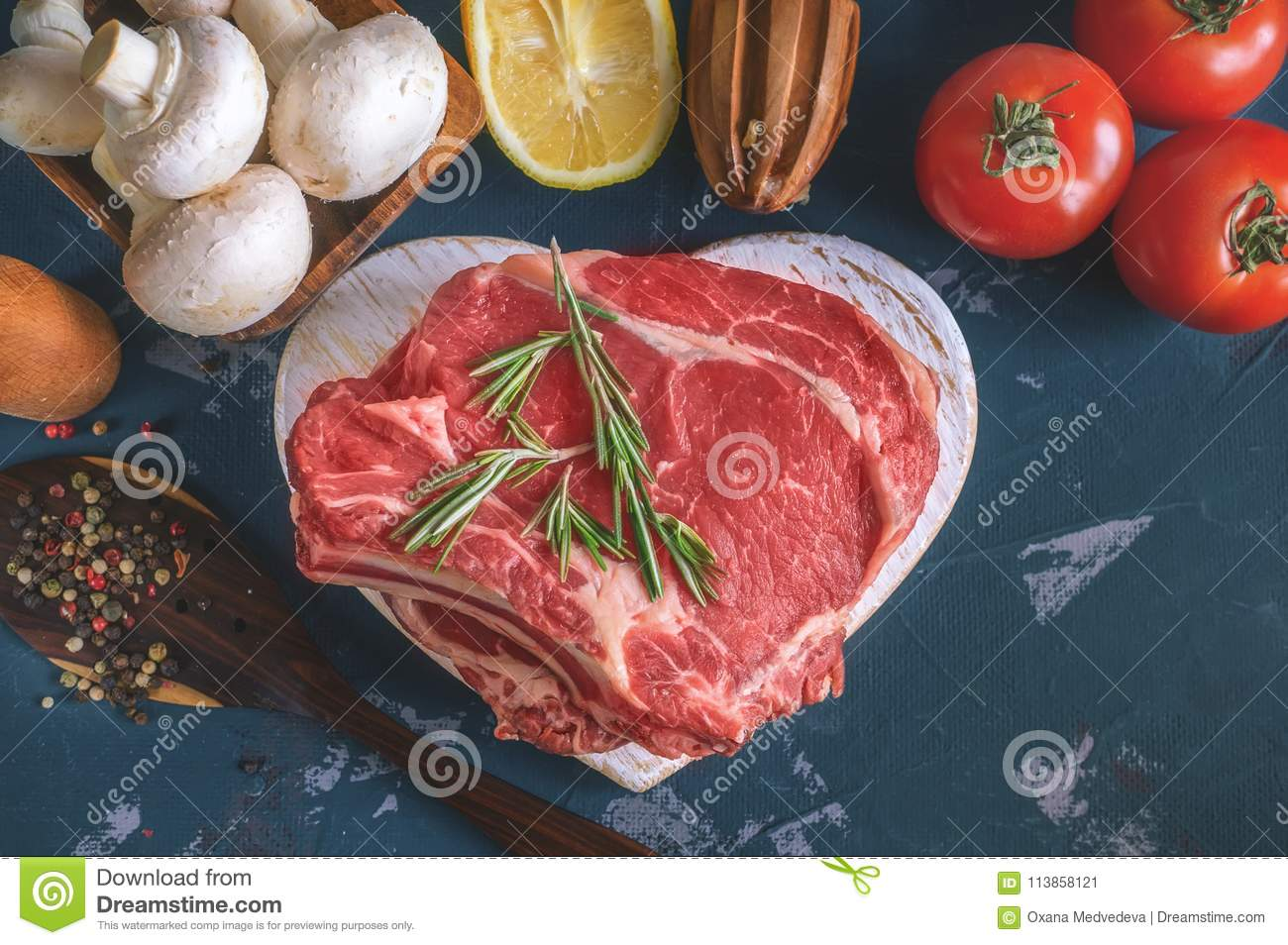 Cuts of beef for grilling on a wooden cutting Board with the Bay leaf, rosemary, olive oil and Provencal herbs for the
