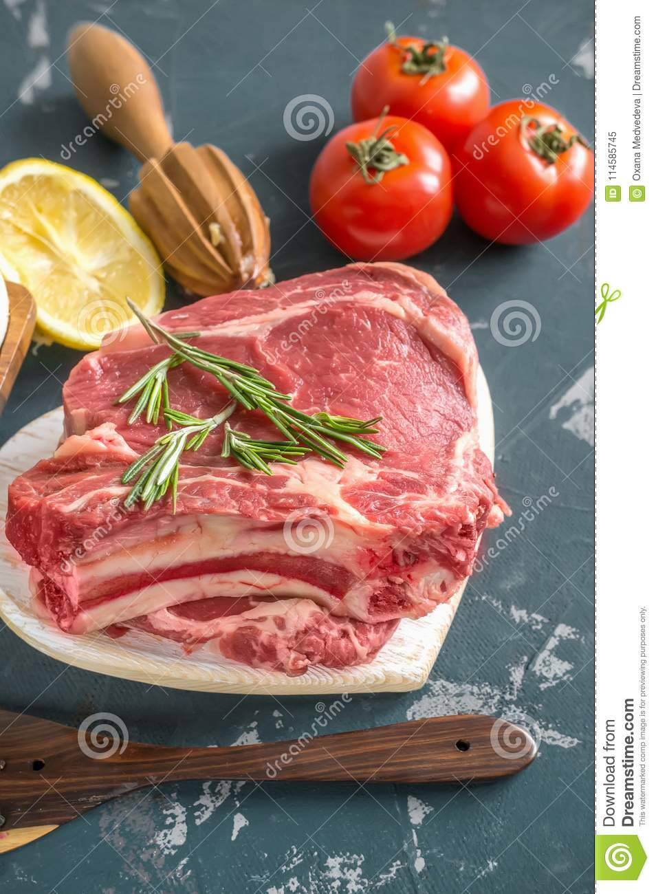 Cuts of beef for grilling on a wooden cutting Board with the Bay leaf, rosemary, olive oil and Provencal herbs for the marinade in