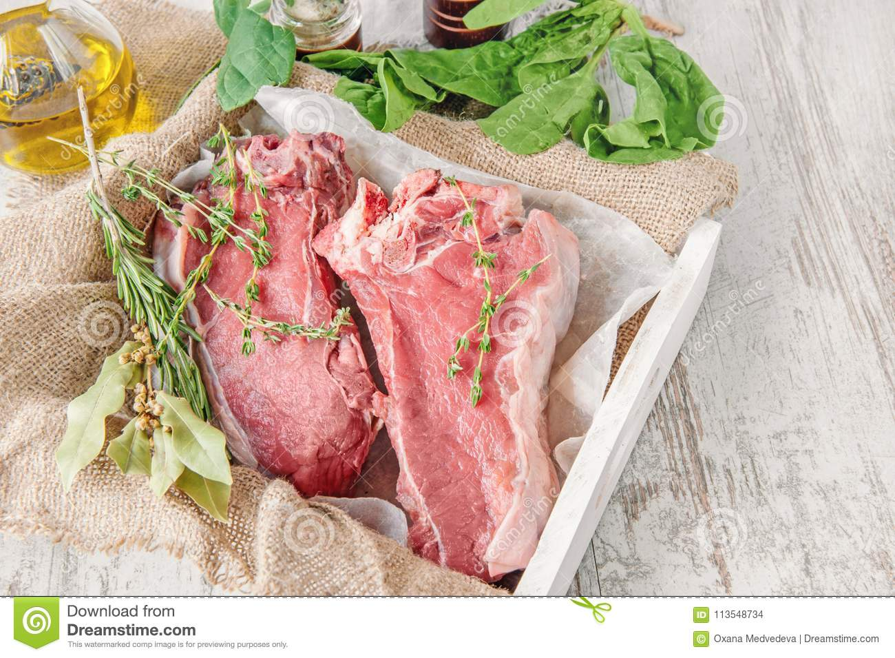 Cuts of beef for grilling on a wooden cutting Board with spinach, rosemary and Provencal herbs for the marinade in a