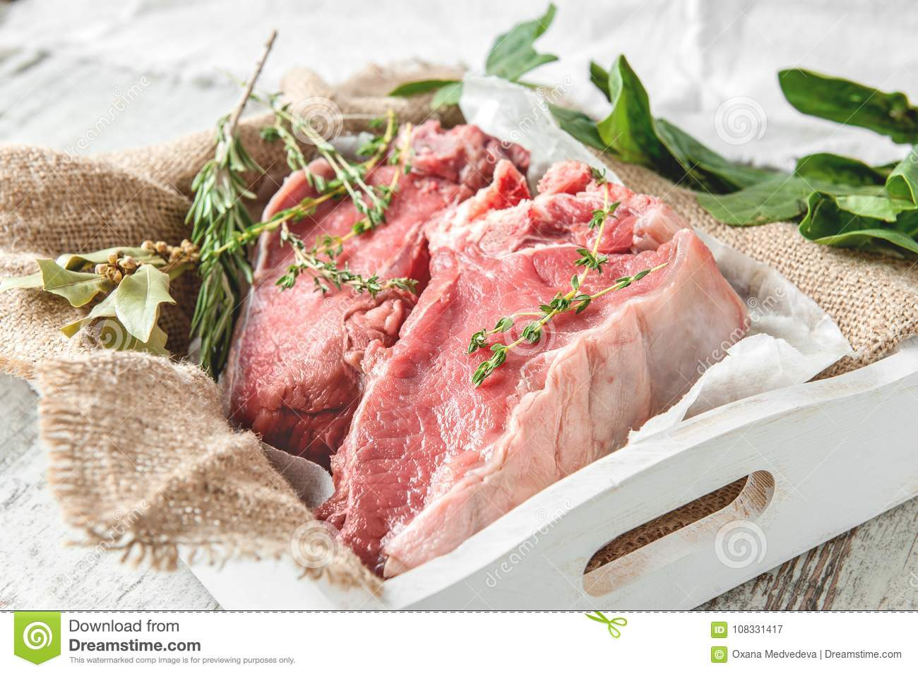 Cuts of beef for grilling on a wooden cutting Board with spinach, rosemary and Provencal herbs for the marinade in a rustic style.
