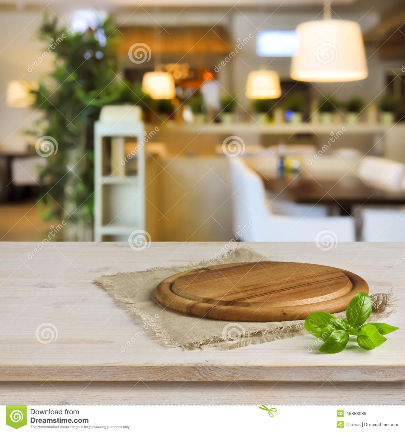 stock photo kitchen table round board over green bokeh background image kitchen table restaurant Cutting board on table over blurred restaurant interior background Royalty Free Stock Images