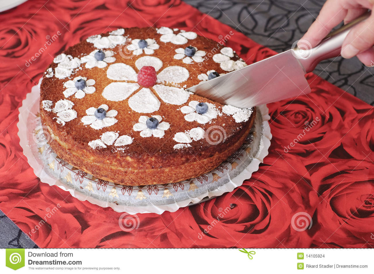 Hand holding knife and cutting a beautiful cake.