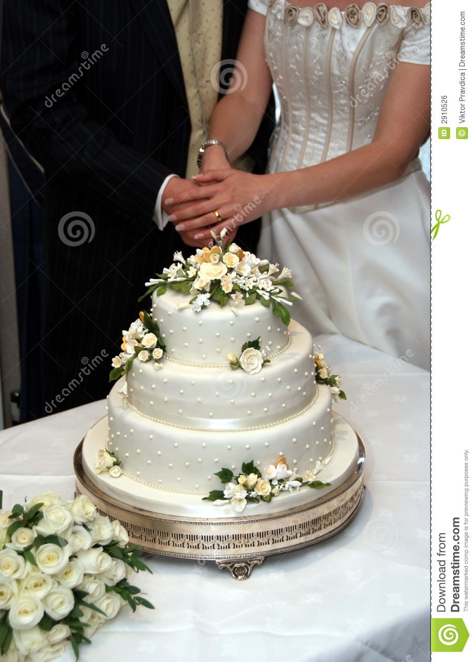 Cutting Into Their Wedding Cake Bride And Groom Shown From The Neck