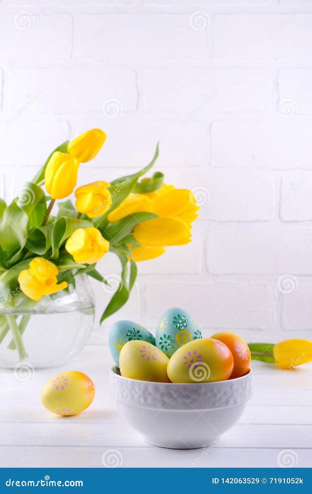 Cuvette avec les oeufs de pâques colorés, décoration de Pâques de ressort sur la table en bois blanche avec le bouquet des fleurs