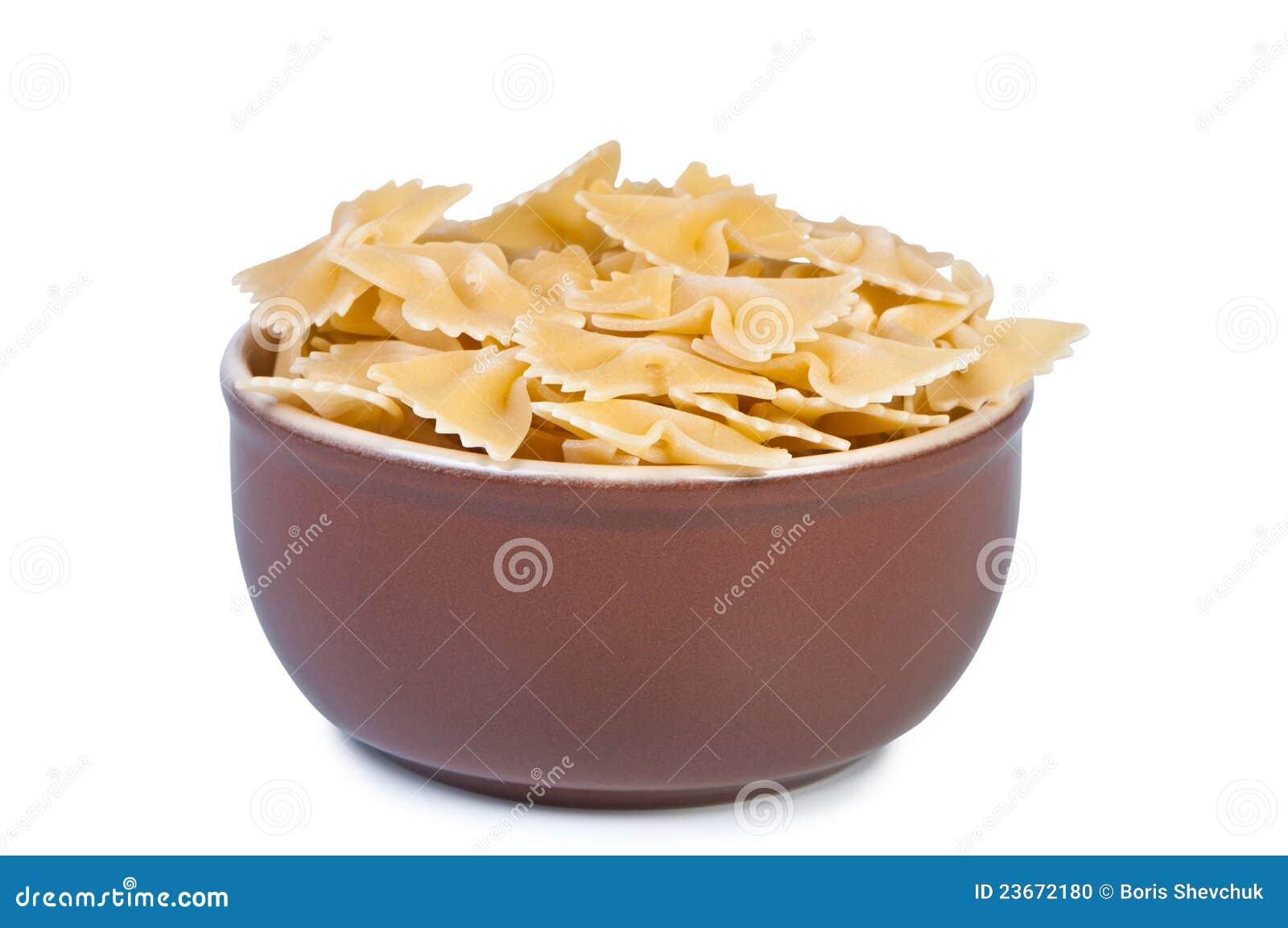 Cuvette avec les pâtes crues sur le fond blanc.