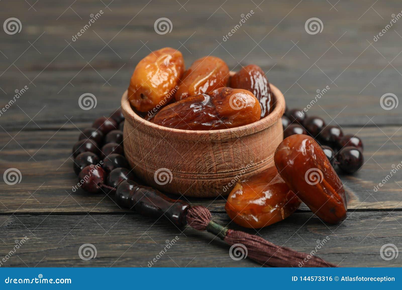 Cuvette en bois avec des dates et des perles de prière