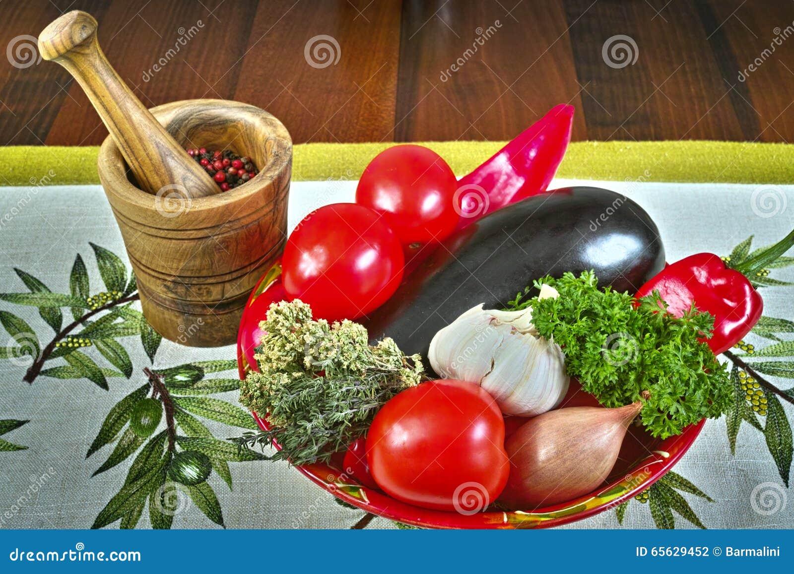 Cuvette ronde rouge avec les légumes frais, mortier en bois olive, nappe avec des olives
