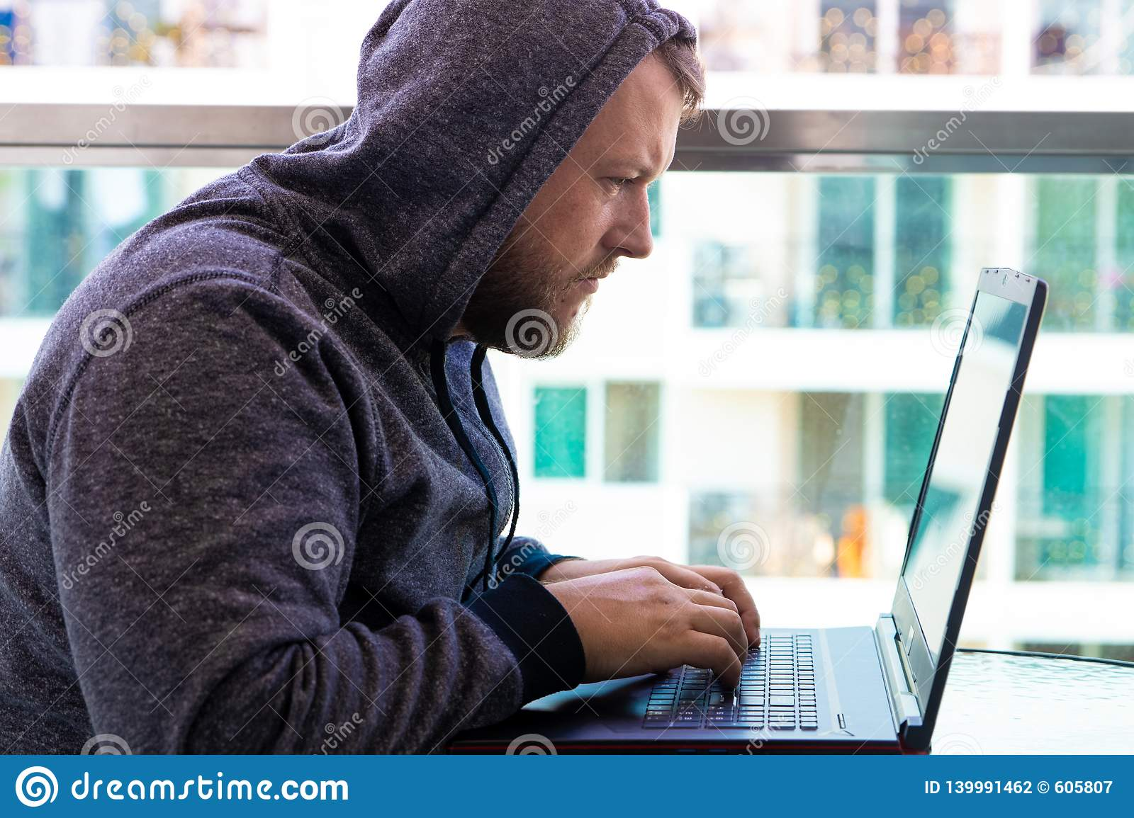 Cybercrime, hacking and technology concept - male hacker writing code or using computer virus program for cyber attack