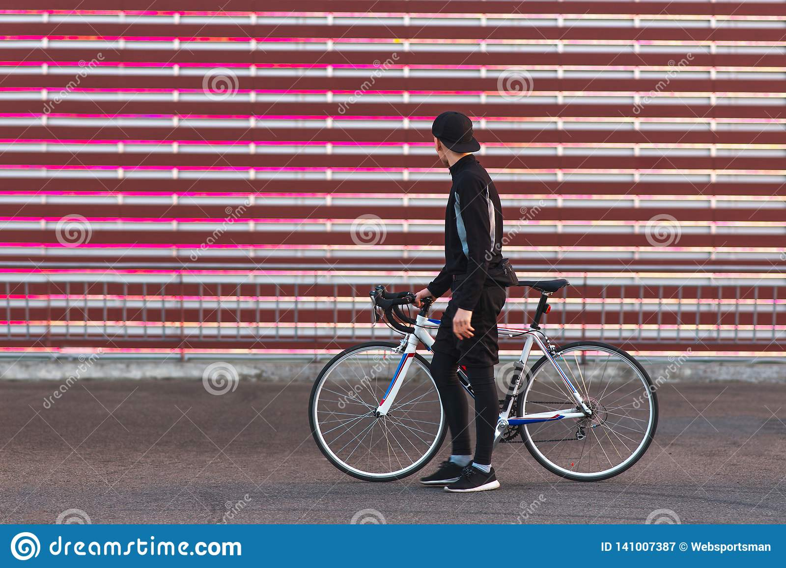 Cyclist in dark sportswear, standing with a bike on the background of a red screen and looking at it