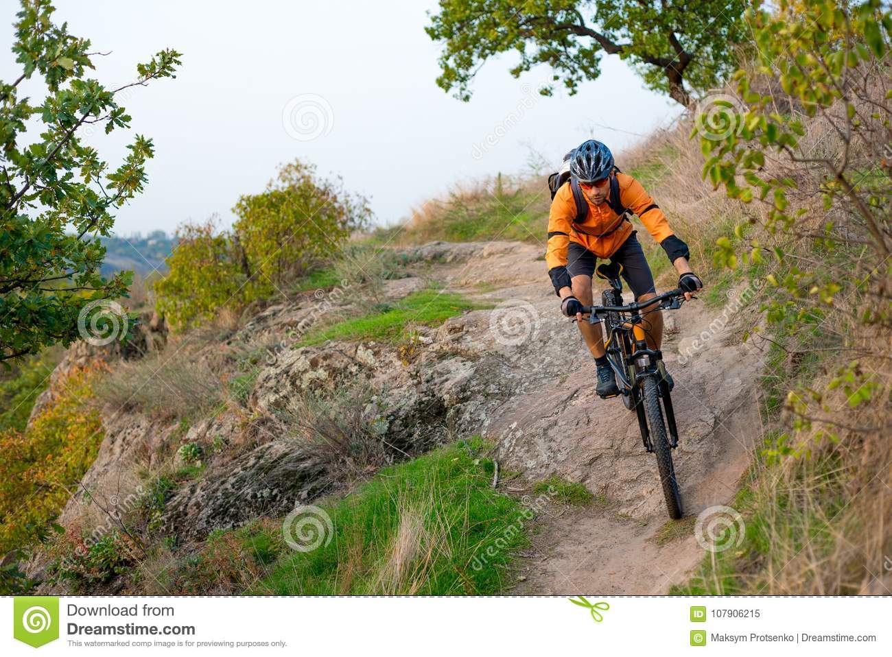 c47cf05a23f Cyclist in Orange Riding the Mountain Bike on the Autumn Rocky Enduro Trail.  Extreme Sport and Enduro Biking Concept.