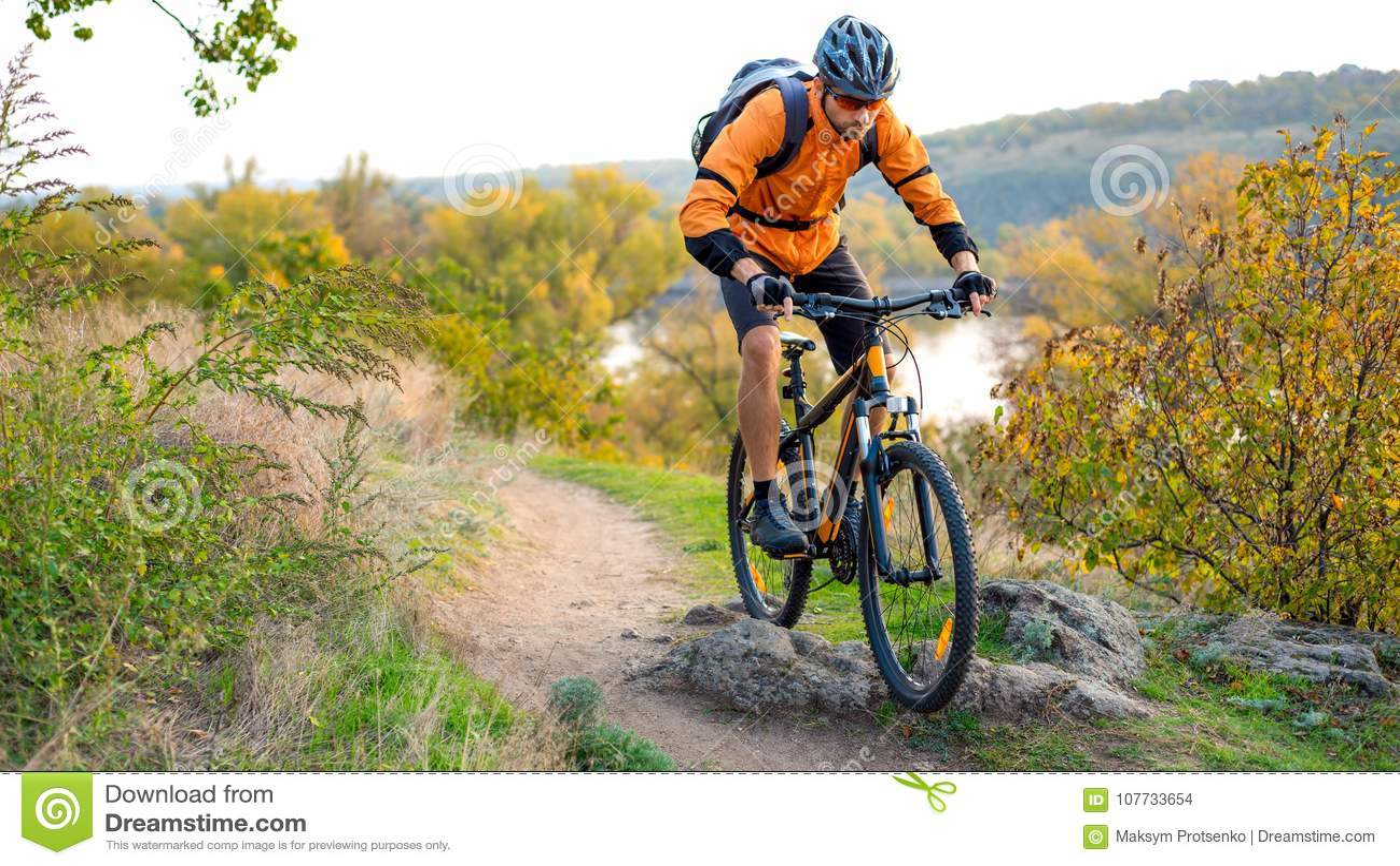 Cyclist in Orange Riding the Mountain Bike on the Autumn Rocky Trail. Extreme Sport and Enduro Biking Concept.