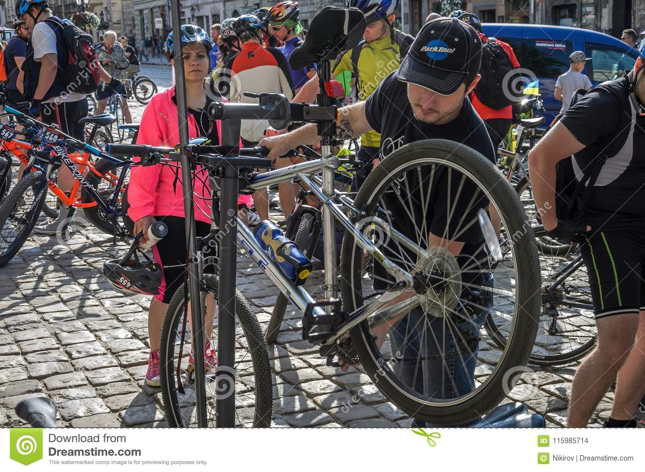 LVIV, UKRAINE - MAY 2018: The cyclist repairs his bicycle by pumping a punctured wheel