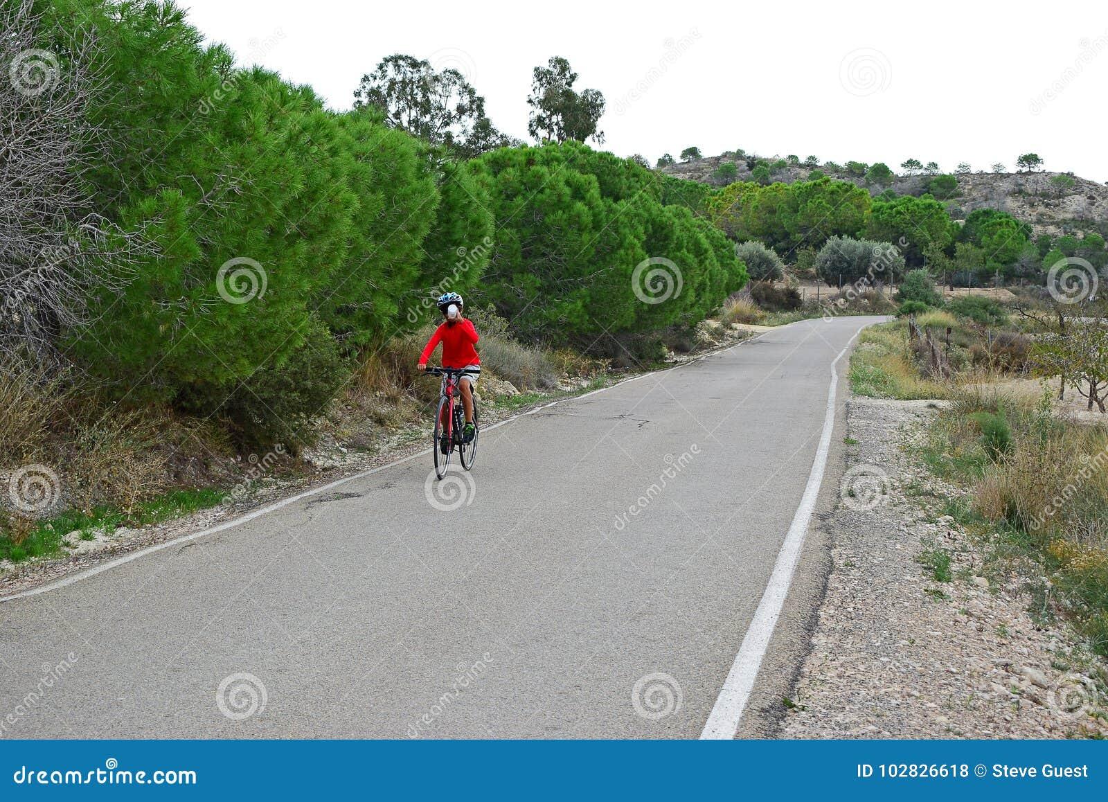 Cycliste buvant d une bouteille tout en faisant un cycle dans les collines