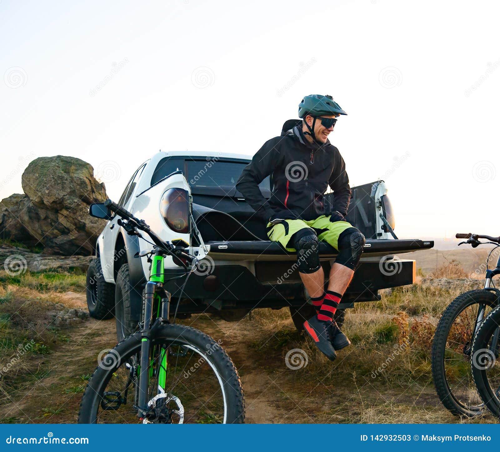 Cycliste sur le camion d Off Road de collecte se reposant après le vélo montant dans les montagnes et parlant avec des amis