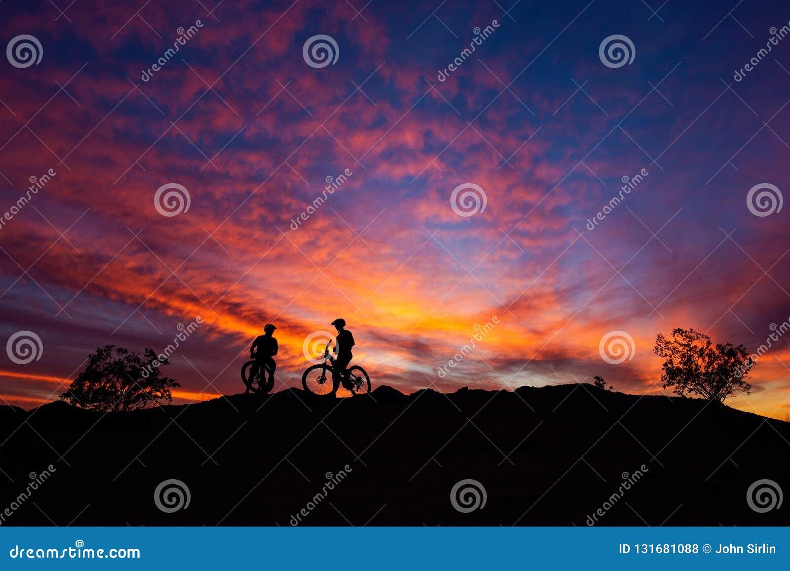 Cyclistes de montagne silhouettés contre un ciel coloré de coucher du soleil en parc du sud de montagne, Phoenix, Arizona