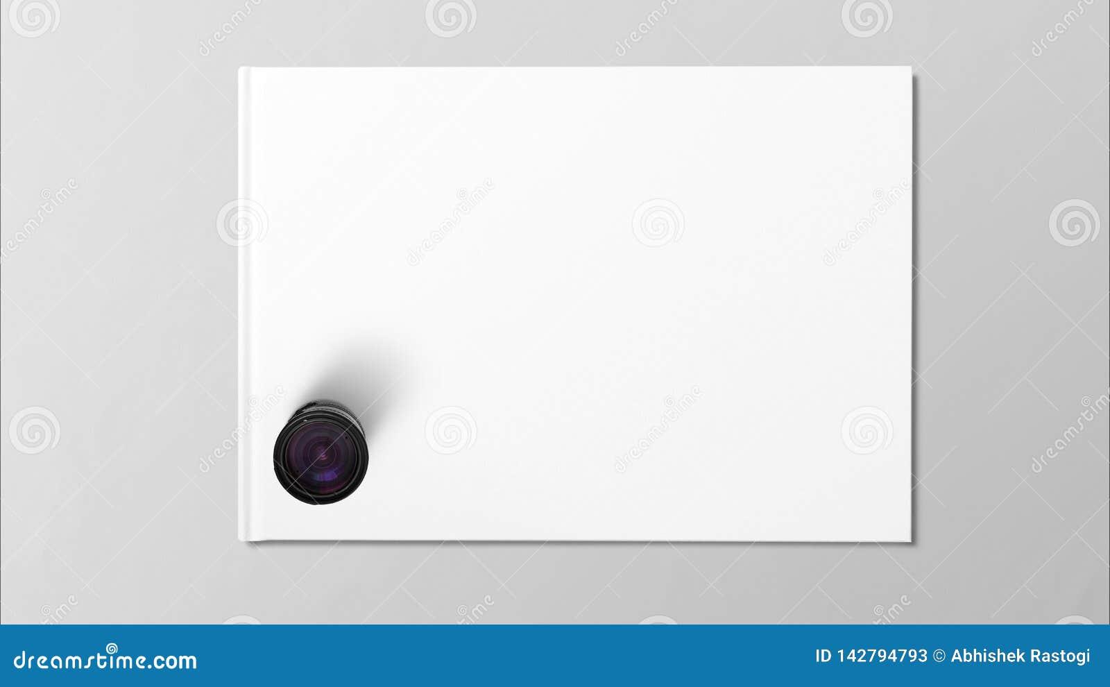 Cyfrowego obiektyw na białej księdze na popielatym tle