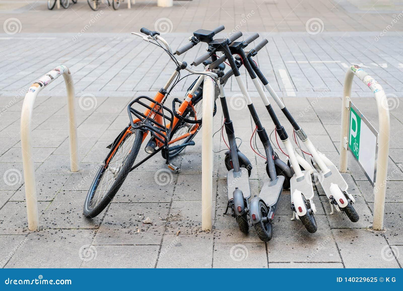 Cykel och elektriska sparkcyklar som parkeras på stadsgatan Uthyrnings- service för självbetjäninggatatransport Stads- medel för