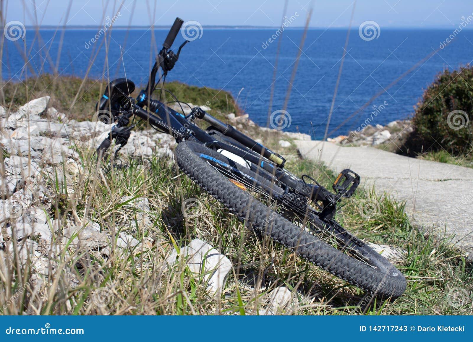 Cykel på en sida av spåret nära havet