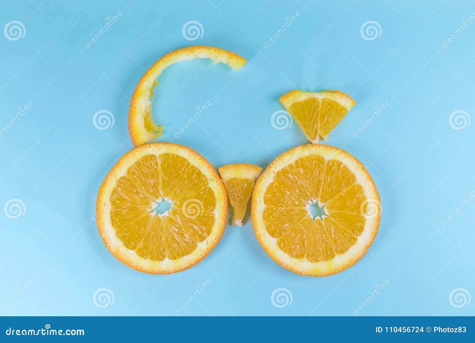 Cykel som göras av den skivade apelsinen på den blåa bakgrunden
