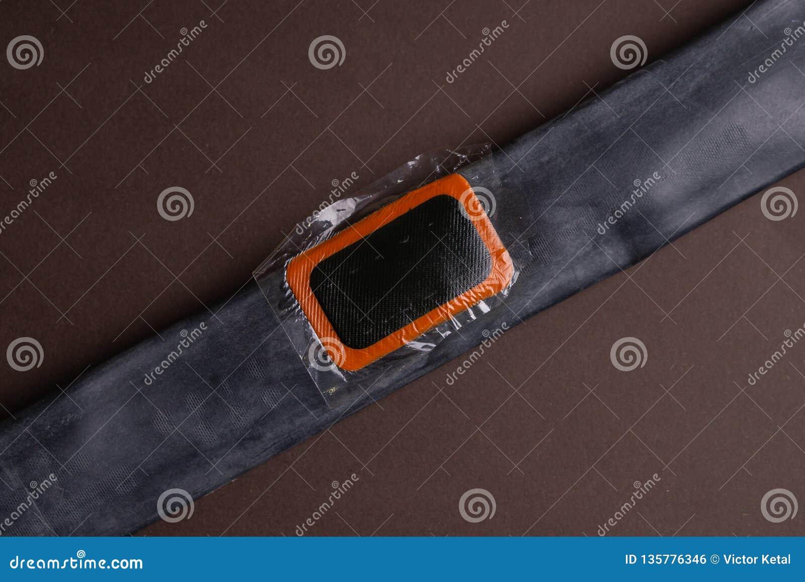 Cykla reparationssatsen, hjulkamera på träbakgrund Lapp på kameran av cykeln