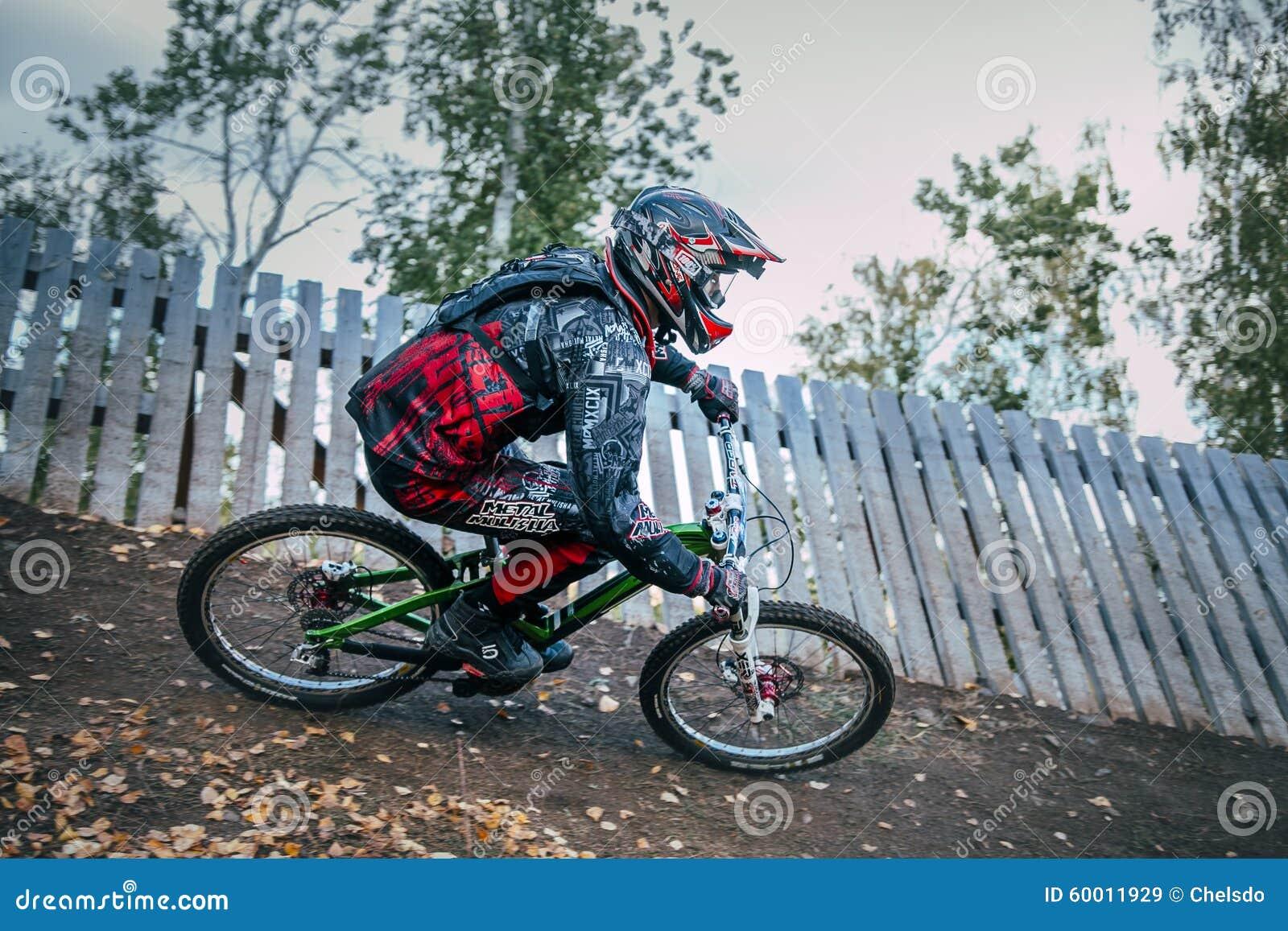 Cyklist som rider en sluttande mountainbike