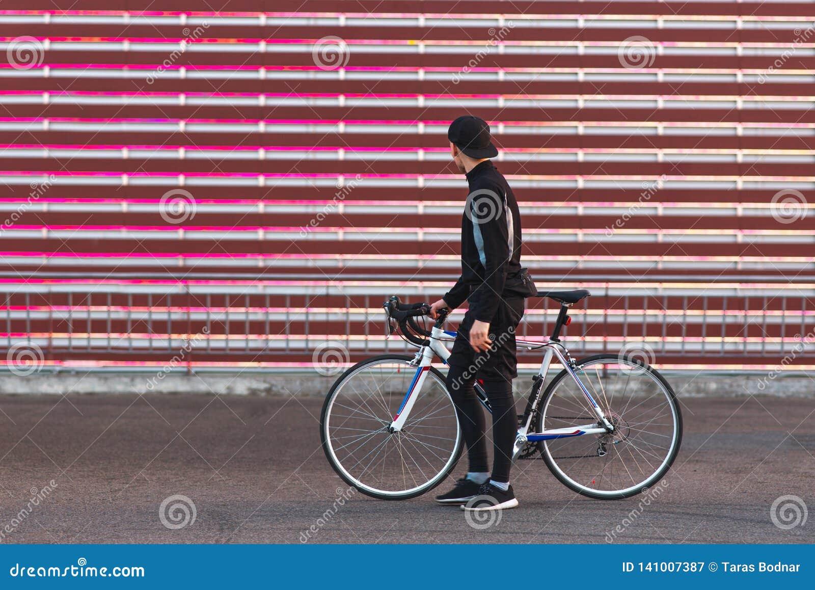 Cyklista w ciemnym sportswear stoi z rowerem na tle czerwony ekran i patrzeje mnie,