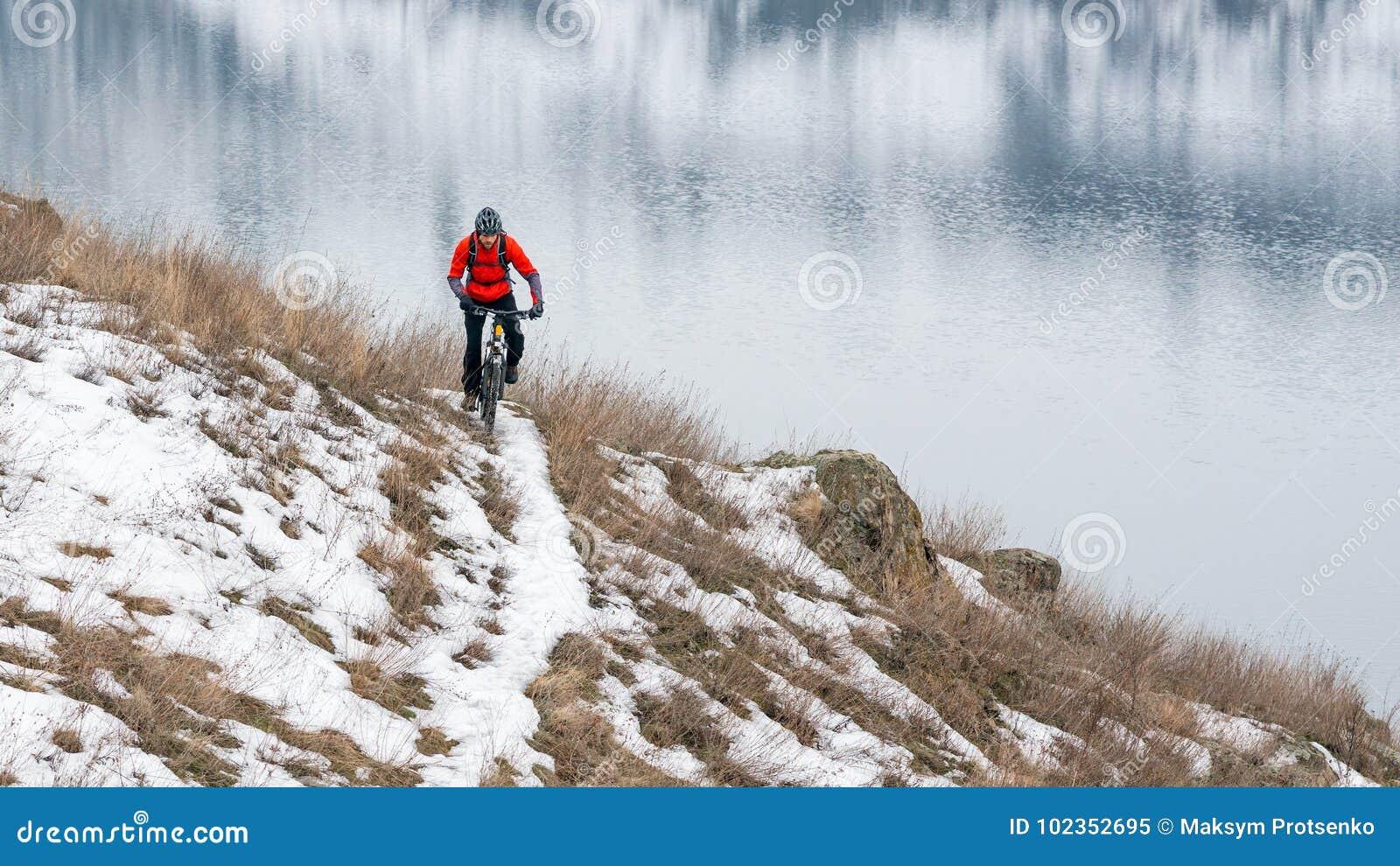 Cyklista w Czerwonym Jeździeckim rowerze górskim na Śnieżnym śladzie Krańcowy zima sport i Enduro Jechać na rowerze pojęcie