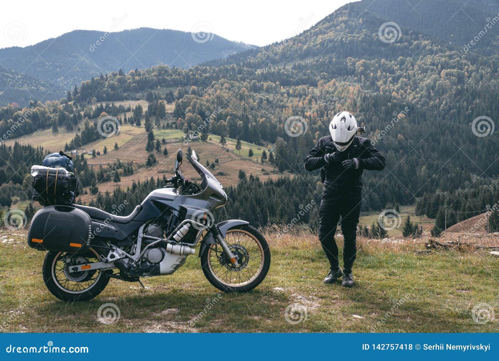 Cyklistman med hans touristic motorcykel, med stora påsar som är klara för en lång tur, svart stil, vit hjälm, ritt, affärsföreta