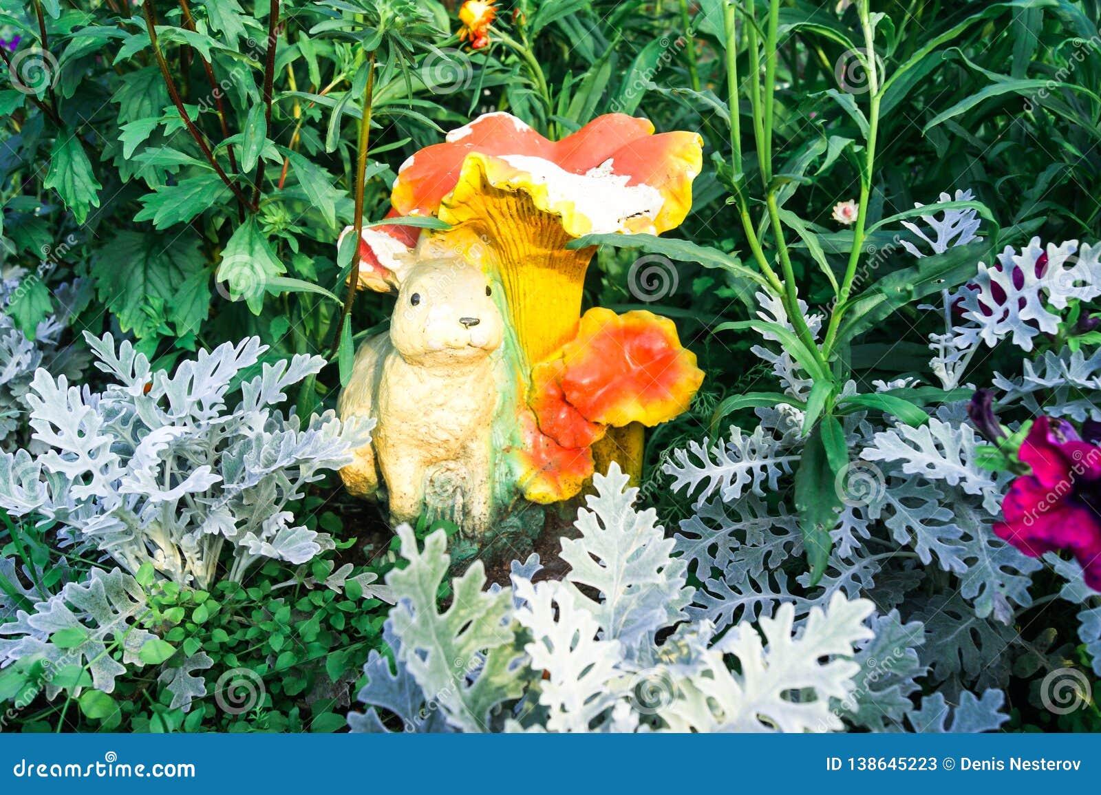 Cynerarie na tle zieleni liście i rzeźbie zając w ogródzie