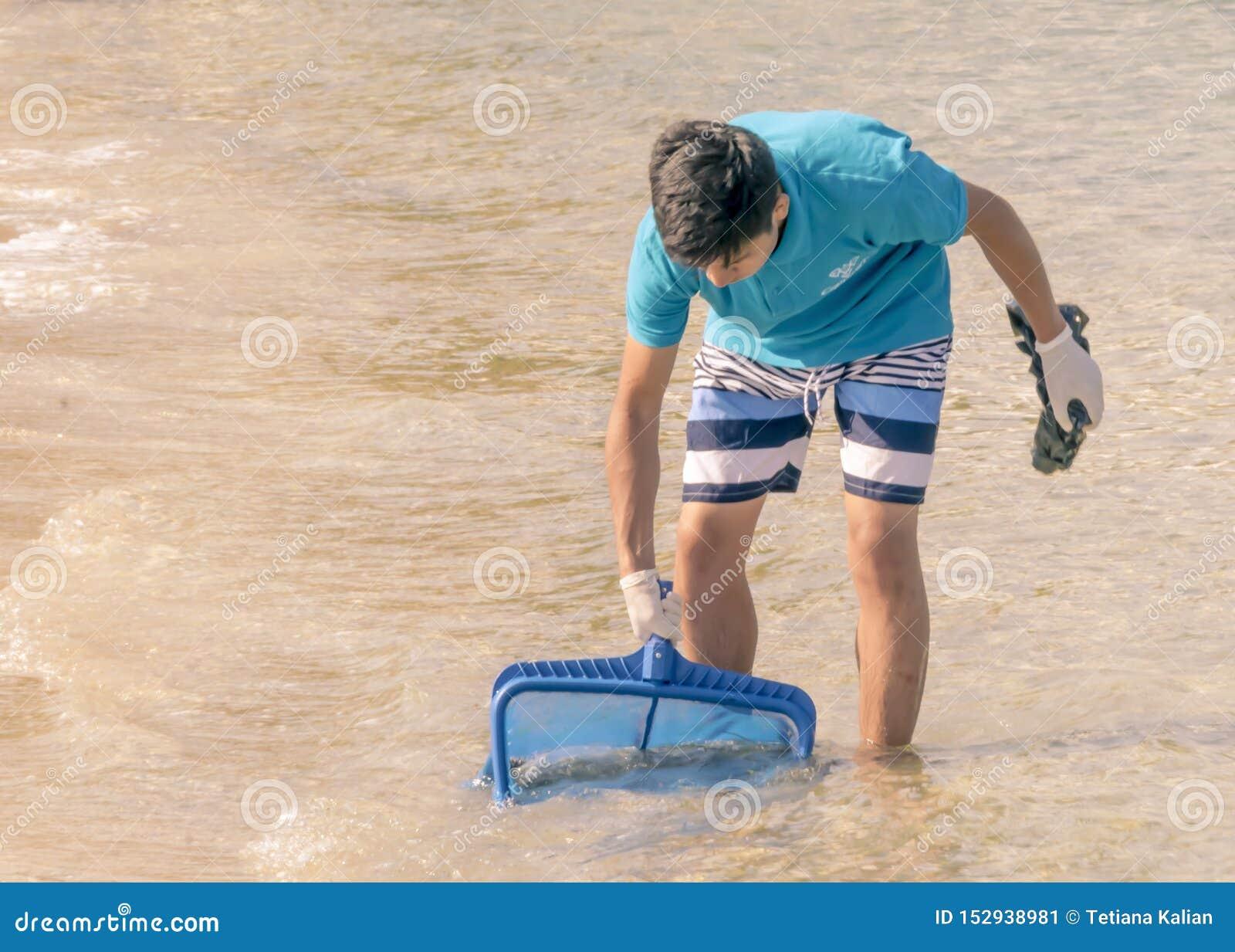CYPR, KARAVAS, ALSANCAK - CZERWIEC 10, 2019: Młoda chłopiec czyści wybrzeże od śmieci Mężczyzna pracuje morzem używać narzędzie