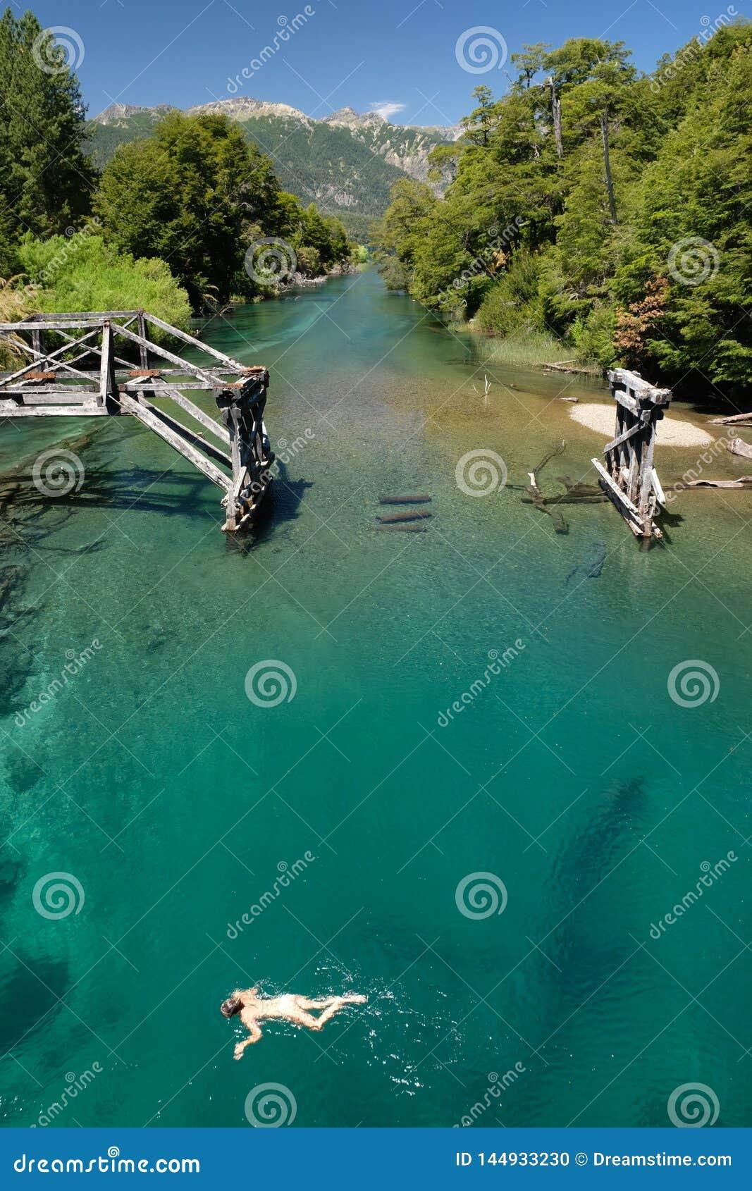 Cyraneczki zielona woda rzeczna w Patagonia, Argentyna z starym mostem i dziewczyną pływa 2