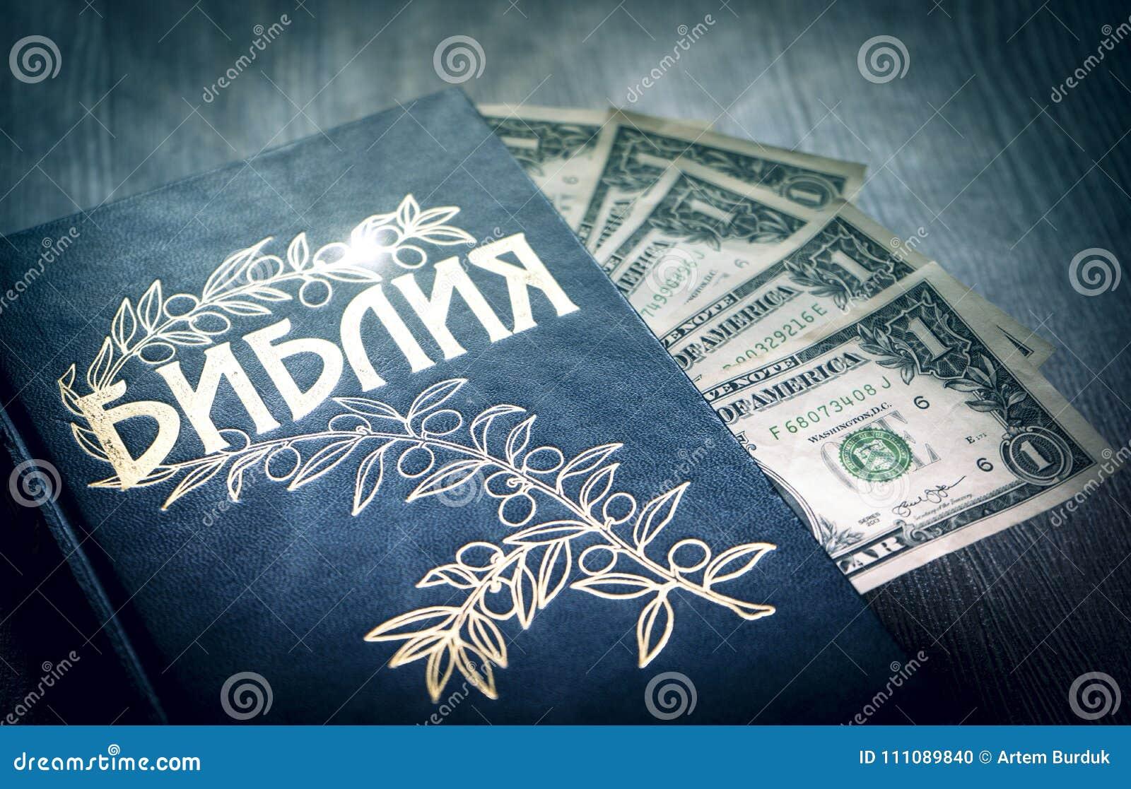 Cyrillic święta biblia z pieniędzy dolarami