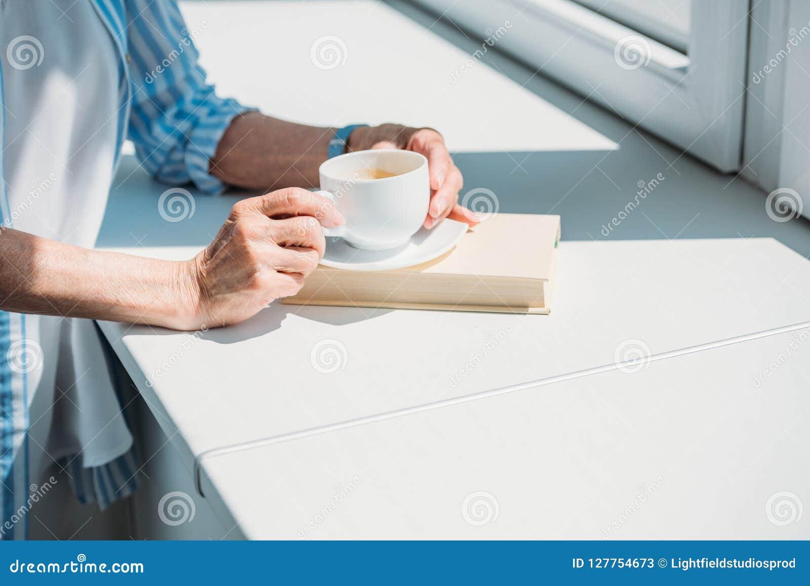 Częściowy widok starsza kobieta z książką i filiżanką kawy na windowsill w domu