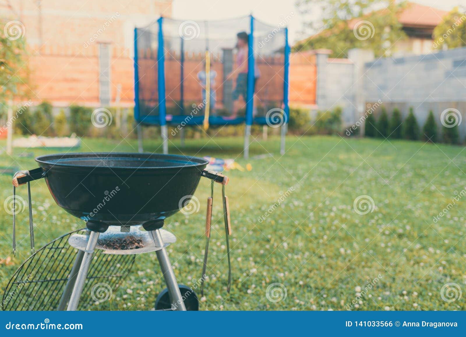 Czajnika węgla drzewnego BBQ grilla grill w ogródzie lub podwórku Zamazany Plenerowy trampoline w tle Dom rodzinny