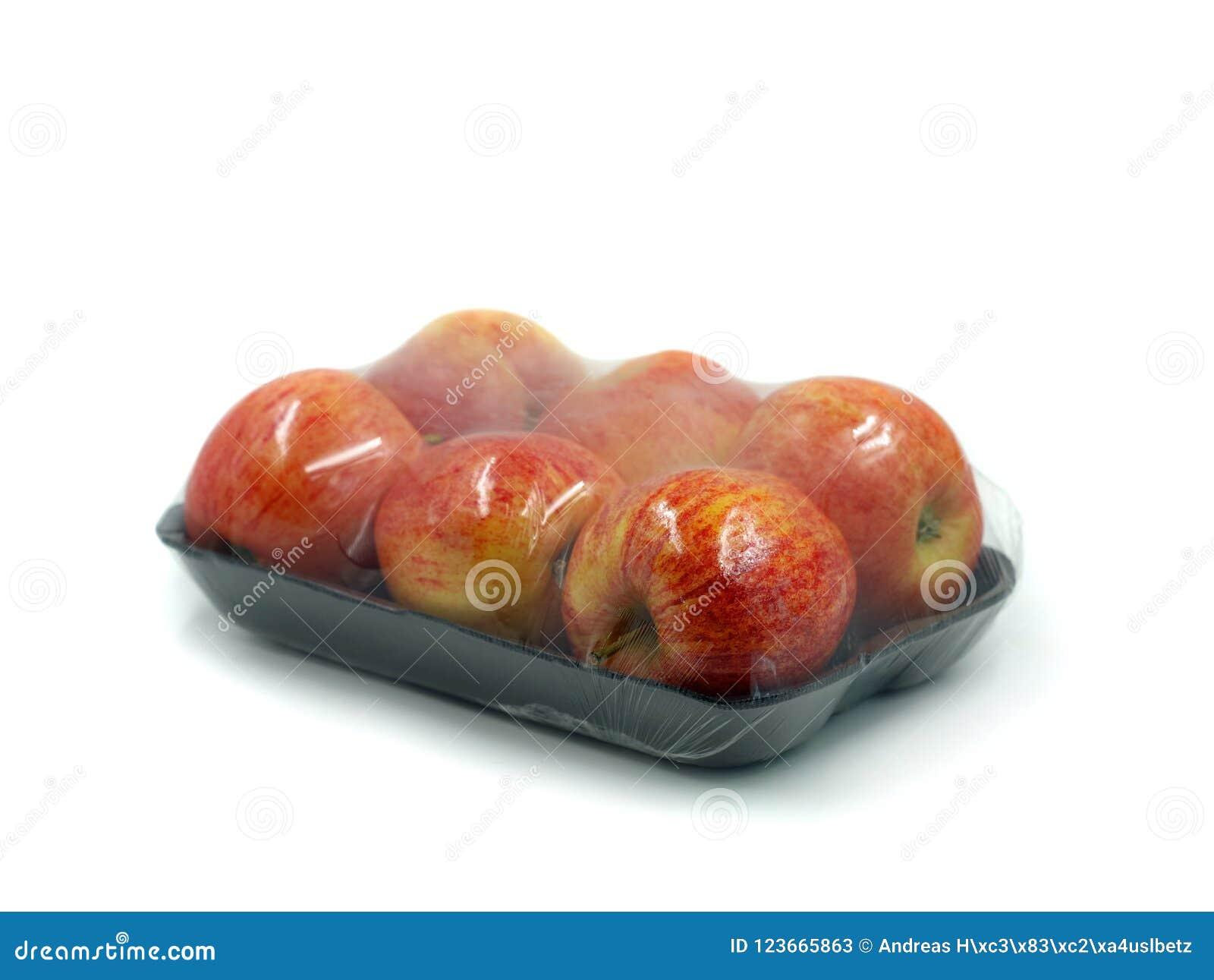 Czarna łupa z sześć jabłkami zawijającymi w przejrzystym klingerycie odizolowywającym na białym tle