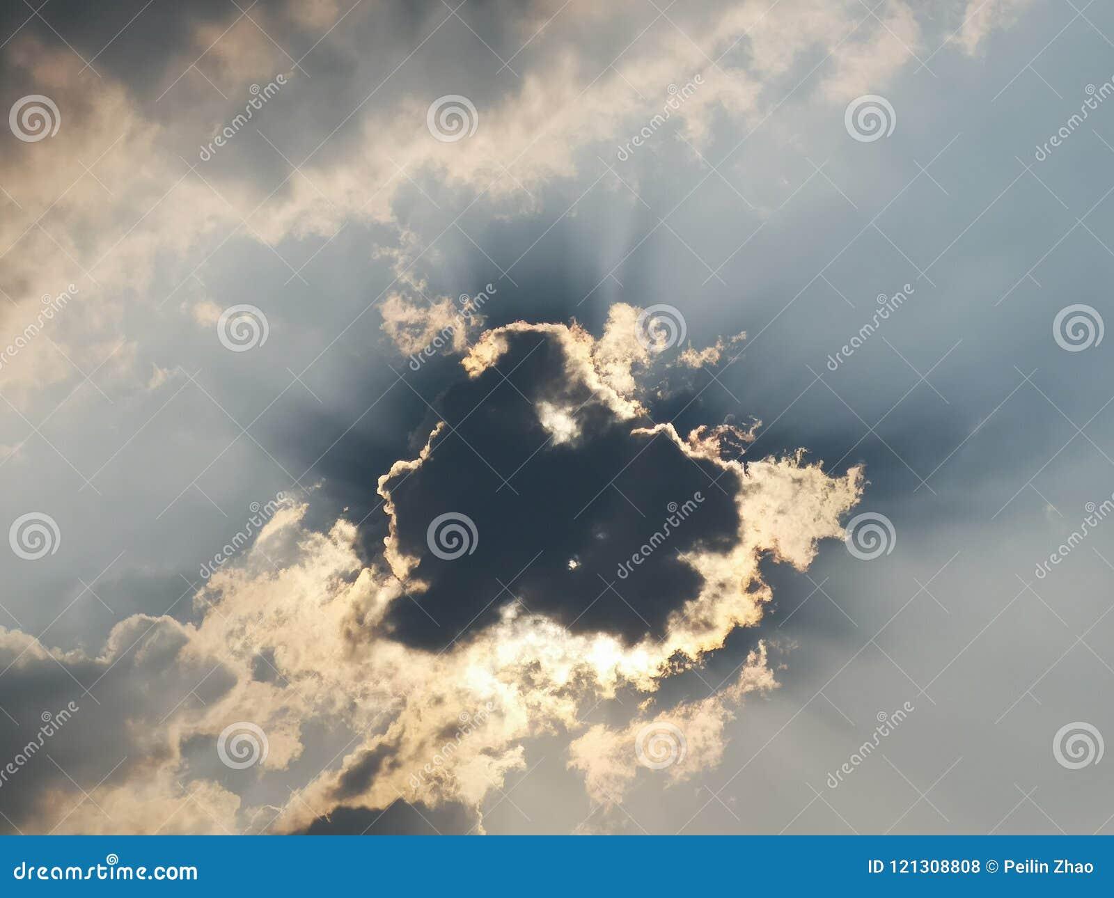 Czarna chmura z światłem słonecznym w niebieskim niebie