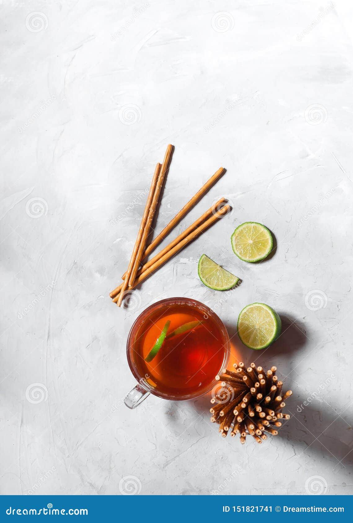 Czarna herbata w szklanym kubku z wapno plasterkami na szarym tle