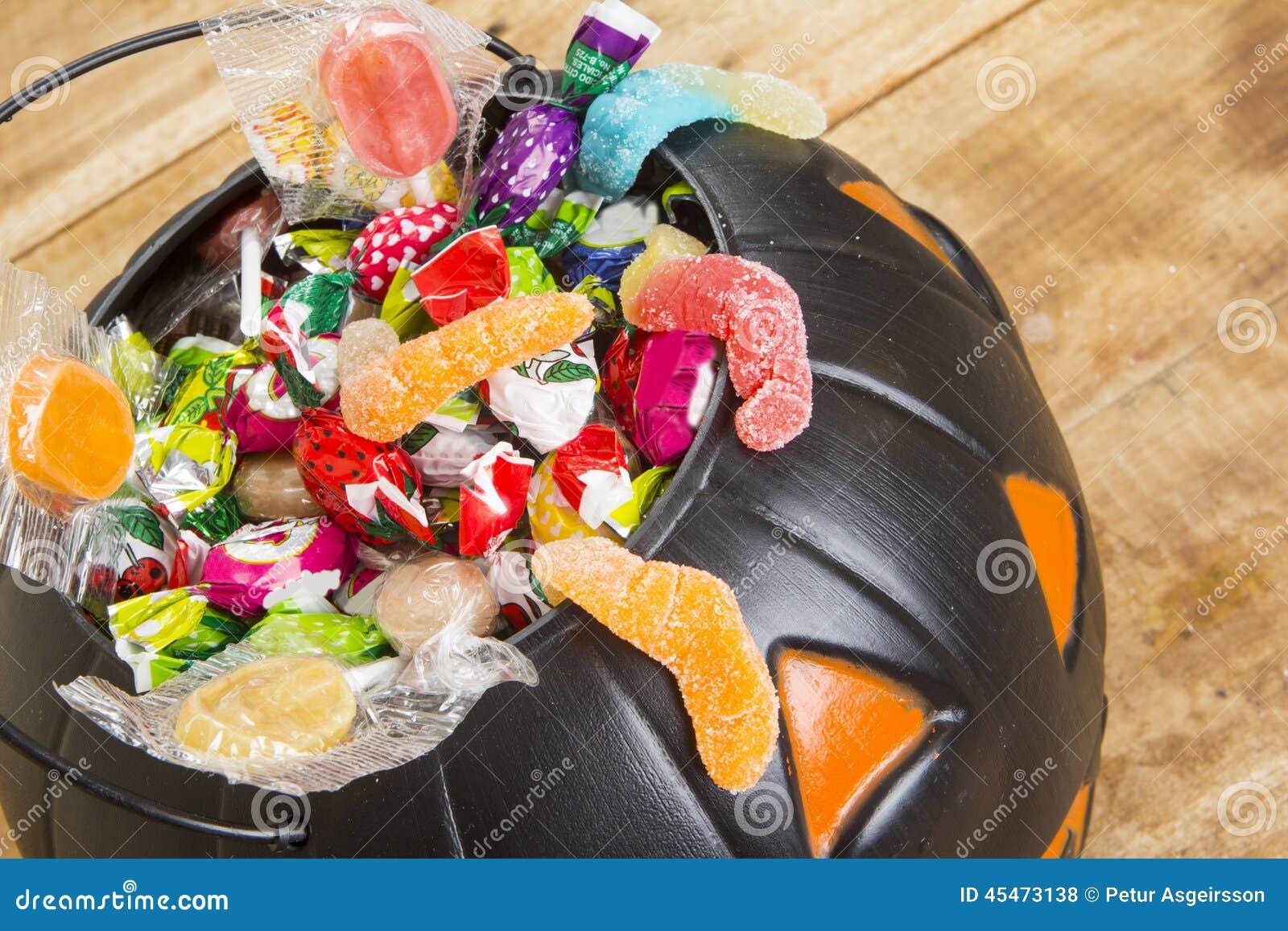 Czarna plastikowa bania wypełniał z cukierkiem na drewnianym stole