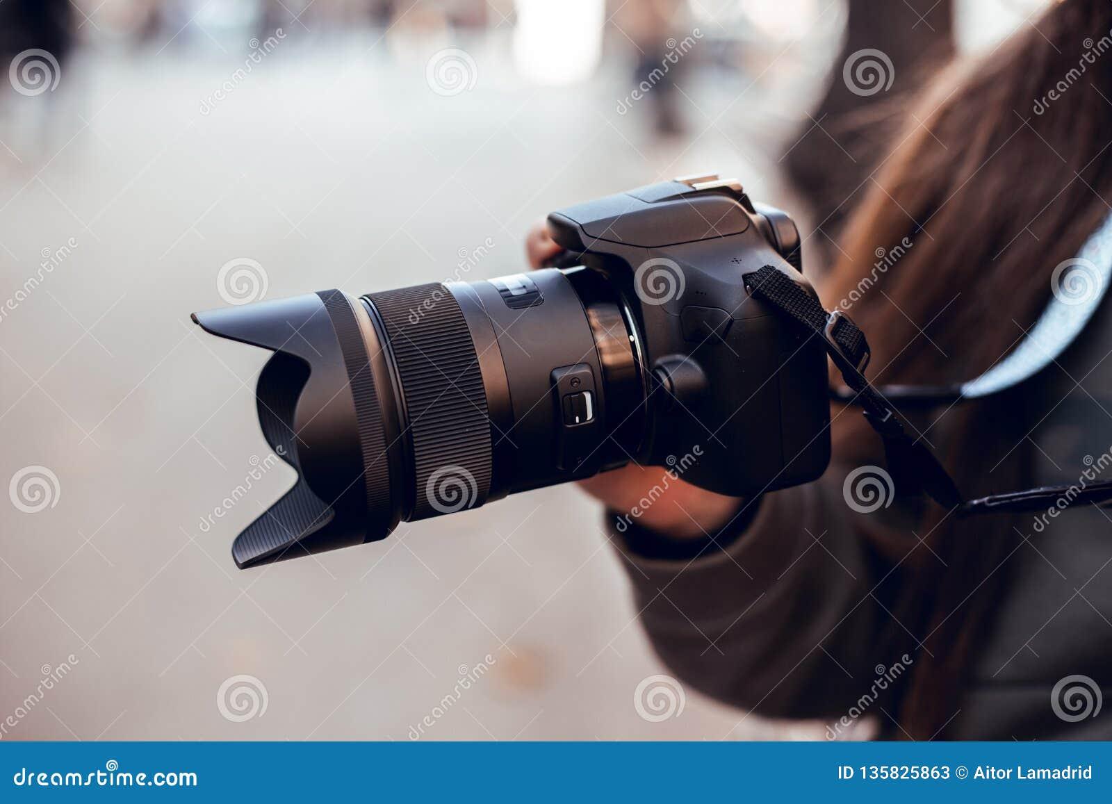 Czarna SLR kamera w rękach dziewczyna