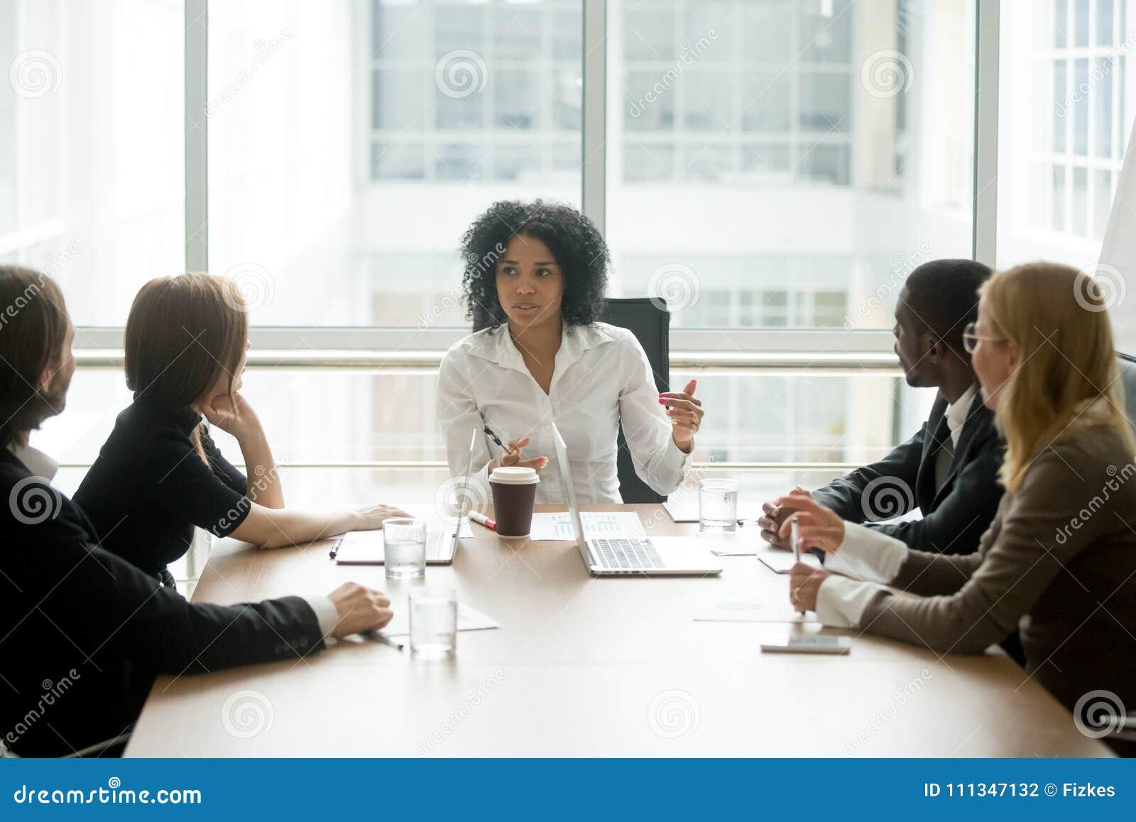Czarnego żeńskiego szefa wiodący korporacyjny spotkanie opowiada różnorodny b