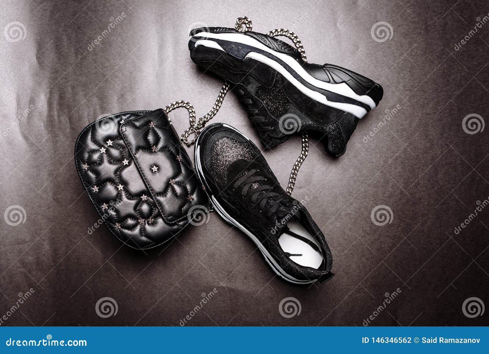 Czarni sneakers na bia?ej g?stej podeszwie dekoruj?cej z czerni? b?yskaj? i czarny sprz?g?o z asteryskami na ?a?cuchu na szaro?ci