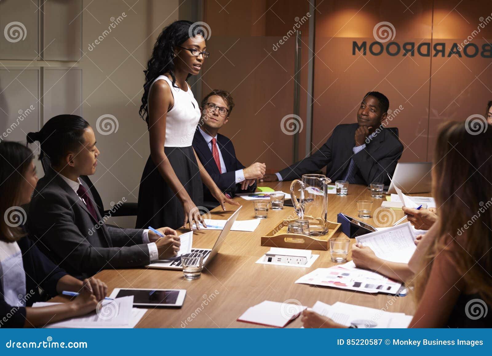 Czarny bizneswoman stoi adresowanie kolegów przy spotkaniem