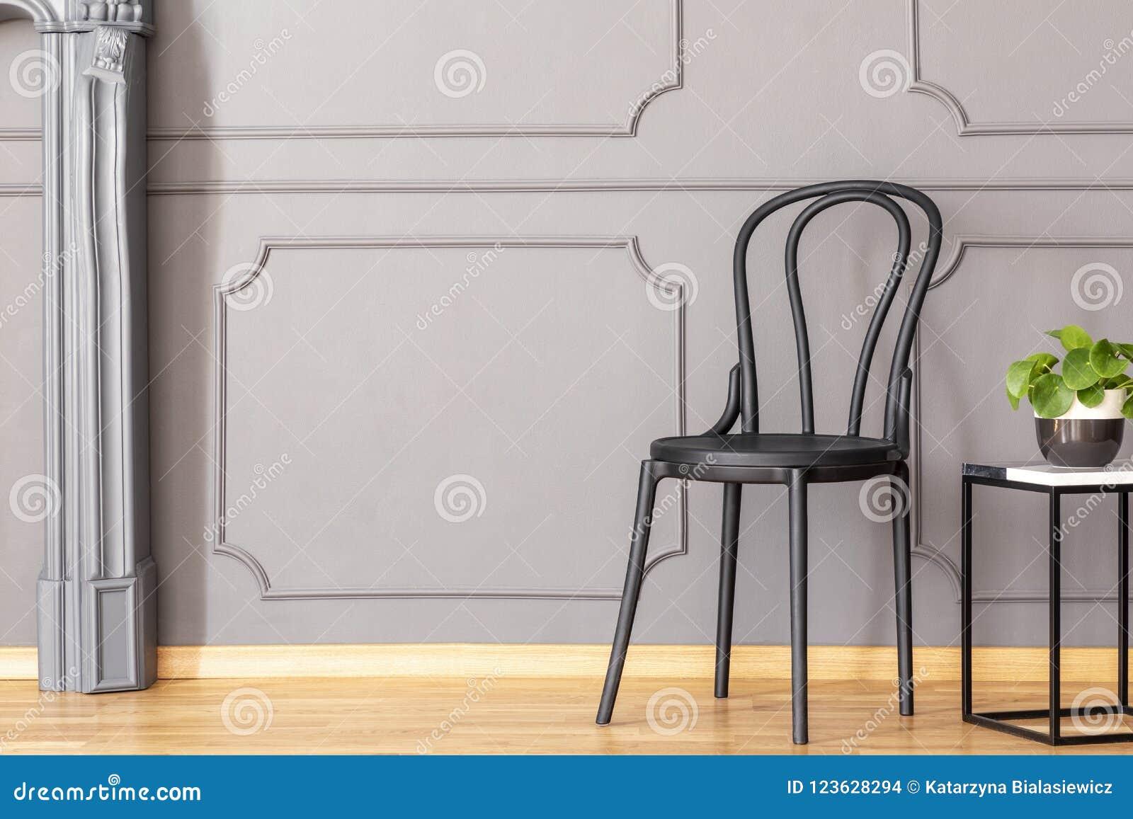 Czarny drewniany krzesła i metalu końcówki marmurowy stół z świeżą zielenią p