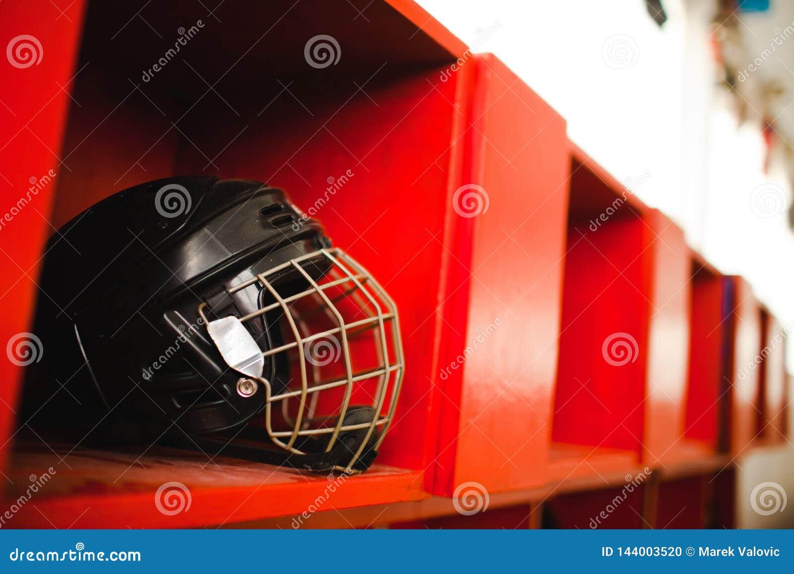 Czarny hokejowy ochrona hełm z klatką na czerwonej półce