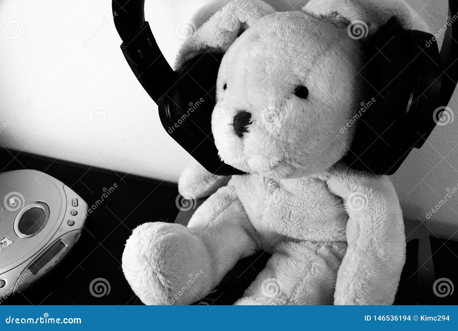 Czarny i biały fotografia faszerująca mokiet zabawka z bezprzewodowymi hełmofonami i wrotnym odtwarzaczem cd