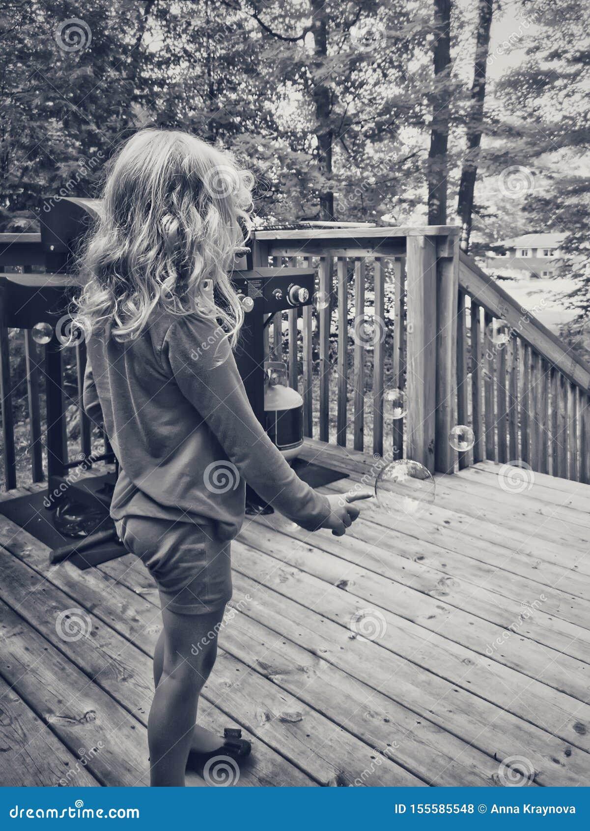 Czarny i biały portret blondynki preschool dziewczyna strzela mydlanych bąble