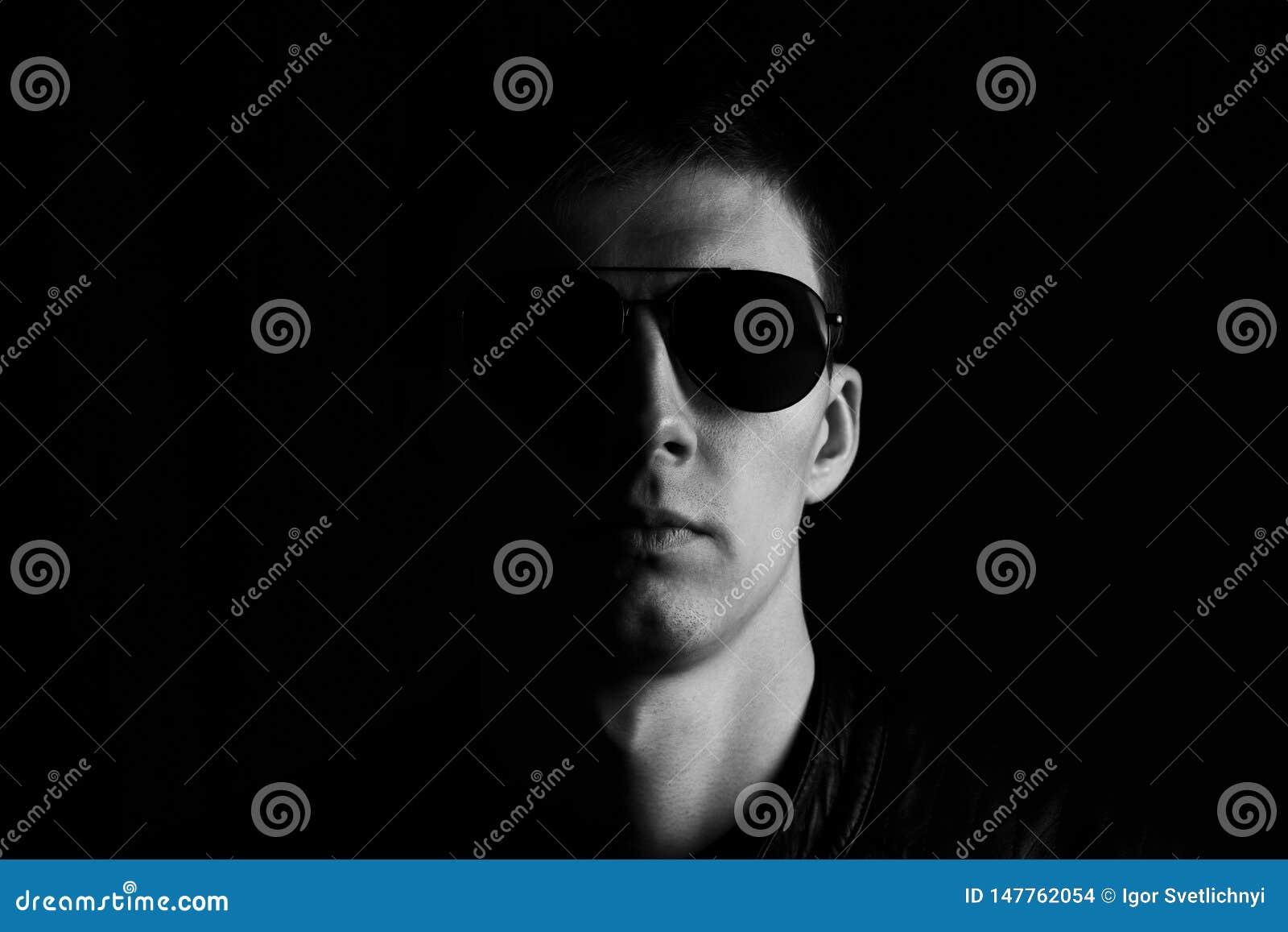 Czarny i biały portret poważny młody człowiek w czarnej skórzanej kurtce i okularach przeciwsłonecznych odizolowywających na czar