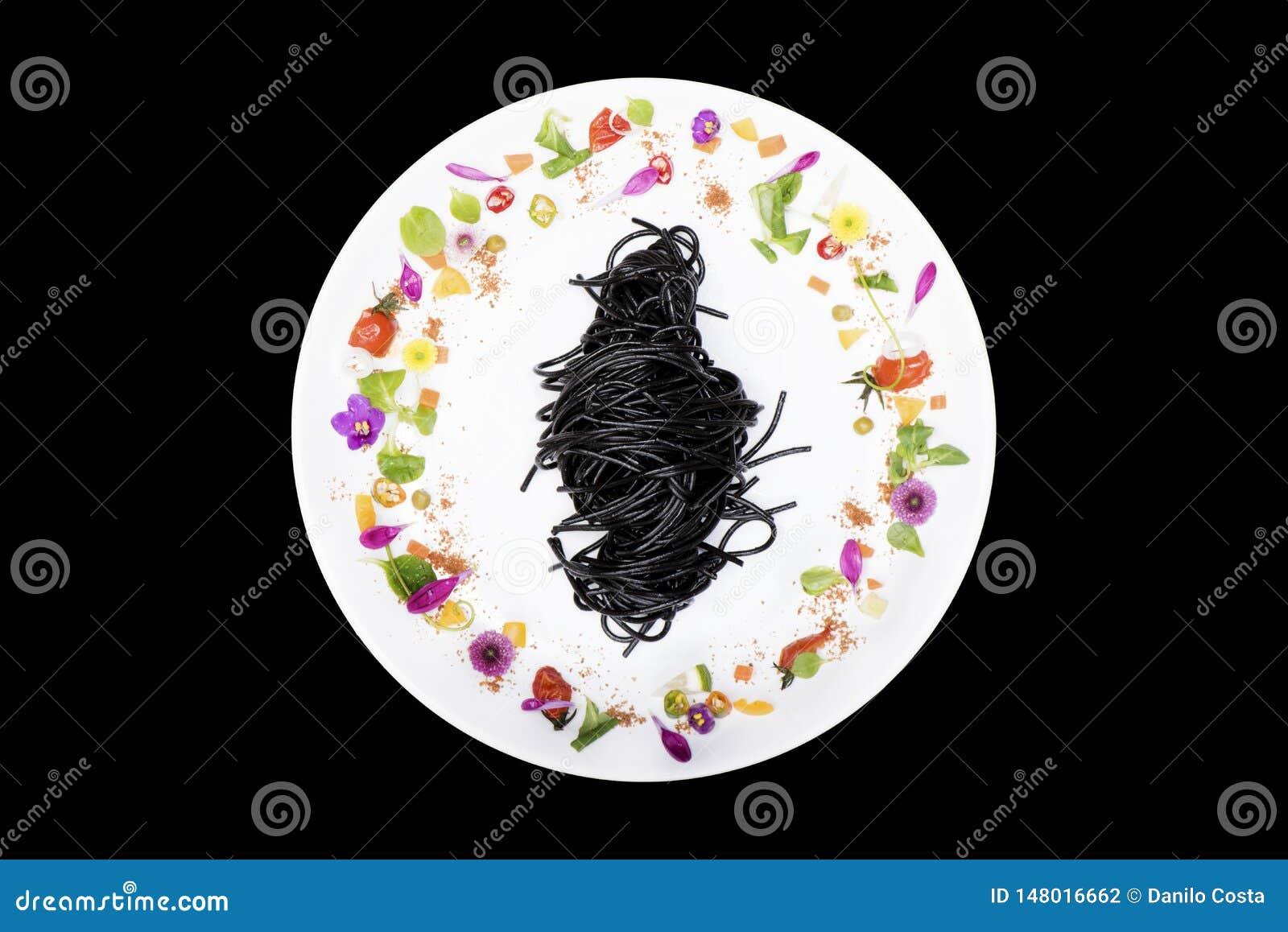 Czarny kałamarnica spaghetti w talerzu z kwiat dekoracją na czarnym tle