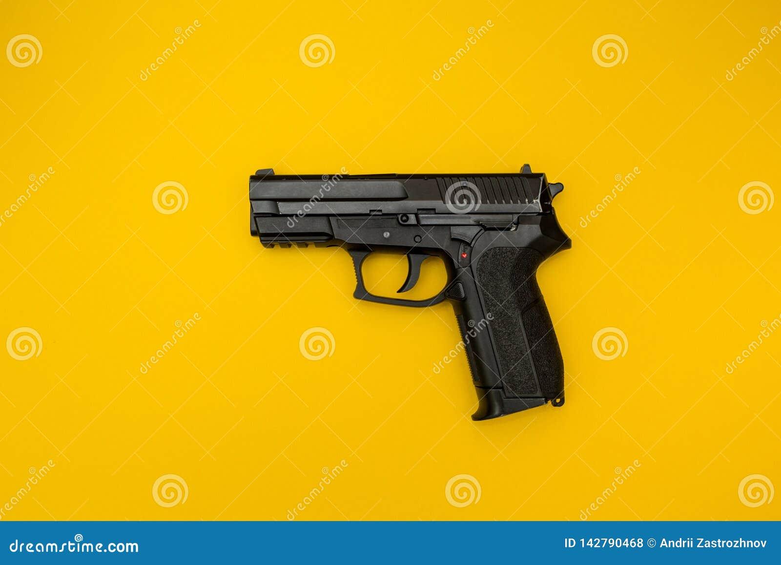 Czarny pistolet na żółtym tle, pojęcie