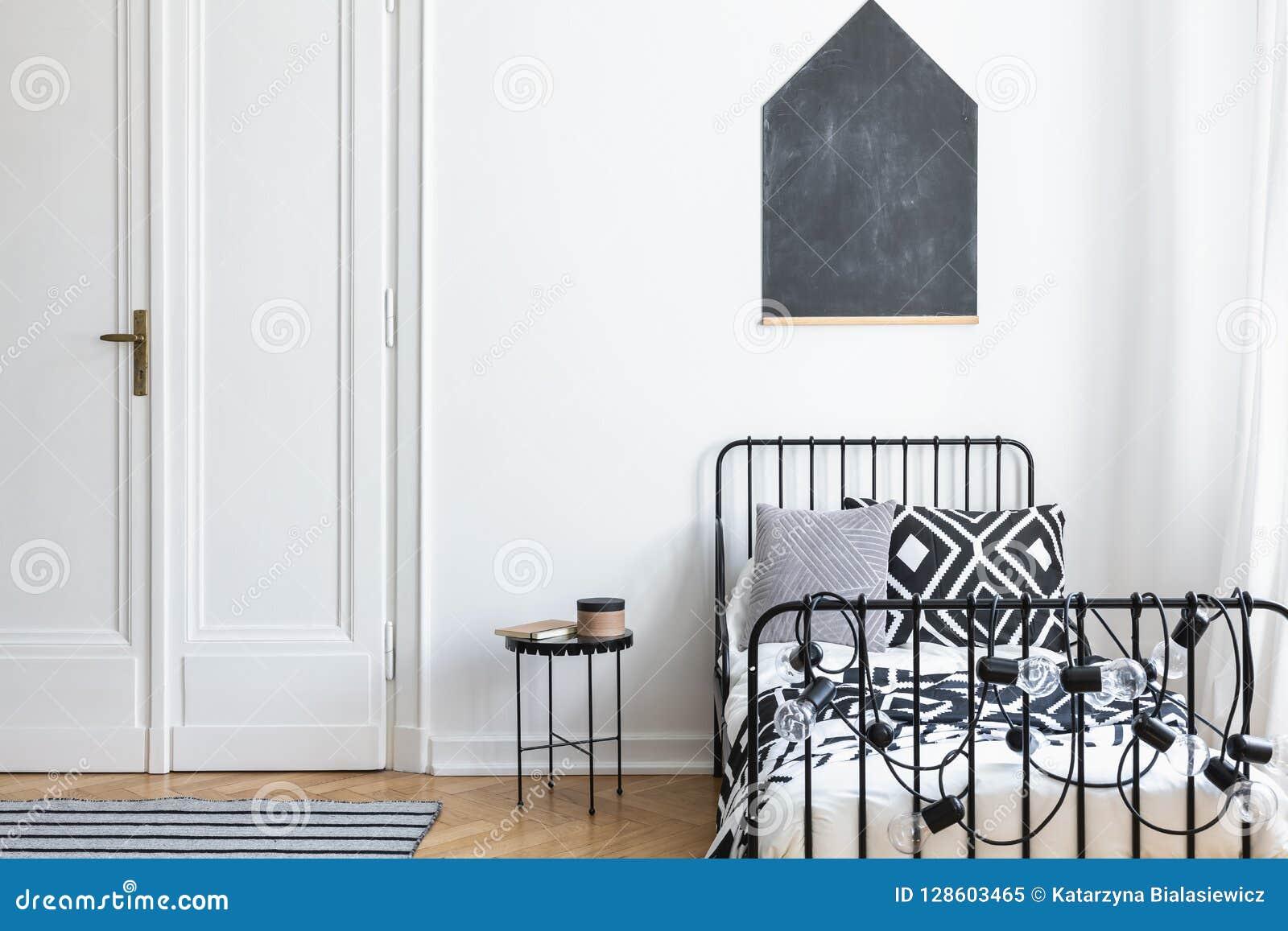 Czarny plakat na biel ścianie nad łóżko w prostym sypialni wnętrzu z drzwi i stołem